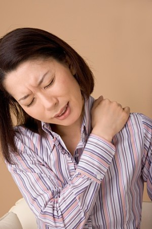 A woman suffering from pain in shoulder